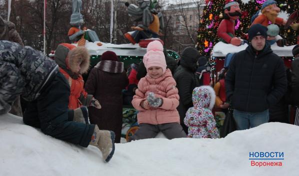 Дети играют  снегу, который счищают с катков.