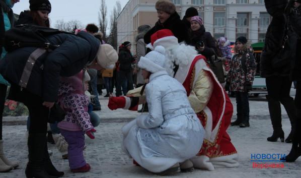 Дед Мороз  Снегурочка дарят малышам конфеты.