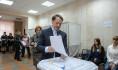 Алексей Гордеев отпускают бюллетень в урну для голосования.