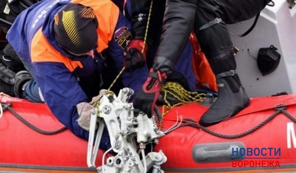 Спасатели поднимают обломки самолета.