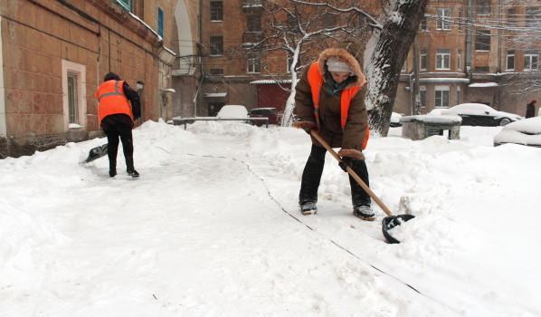 Дворники от нескольких домов расчищают снег.