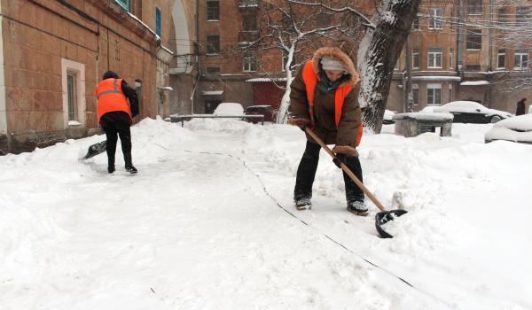 Дворники из соседних домов вместе расчищают снег.