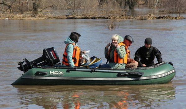 Спасатели помогают людям из затопленных районов.