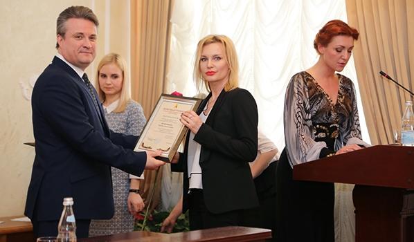 Вадим Кстенин вручает грамоту муниципальному служащему.