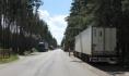 Вдоль дороги массово паркуются грузовики.