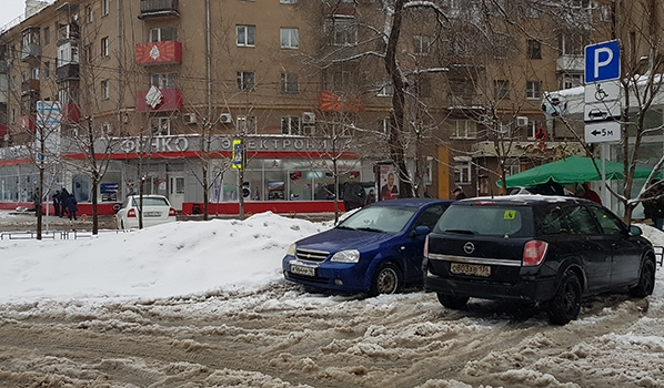 На платной парковке на месте для инвалидов складируют снег.