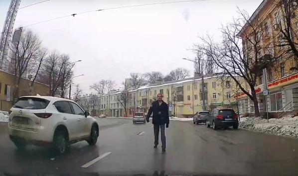 Мужчина брел среди машин.
