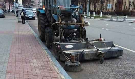 Вращающаяся щетка с бункером на тракторе.