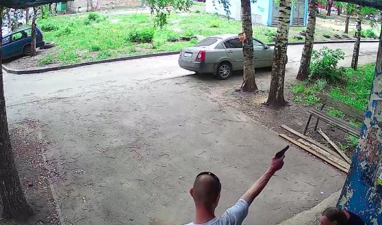 Воронежец стреляет из пистолета во дворе дома.