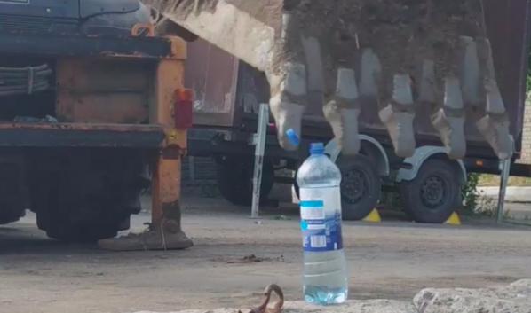 Экскаватор ковшом открыл крышку у бутылки с водой.