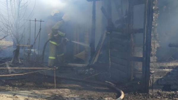Спасатели тушат горящие постройки.