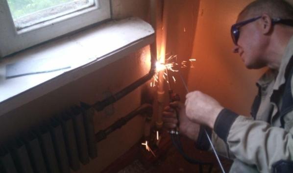 Сотрудник УК восстанавливает радиаторы в подъезде.