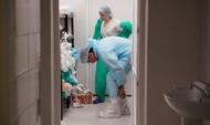 Медики готовятся зайти в отделение для больных коронавирусом.
