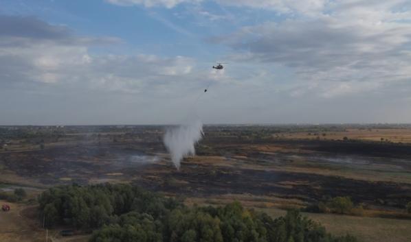 Тлеющие участки заливают водой при помощи вертолета.